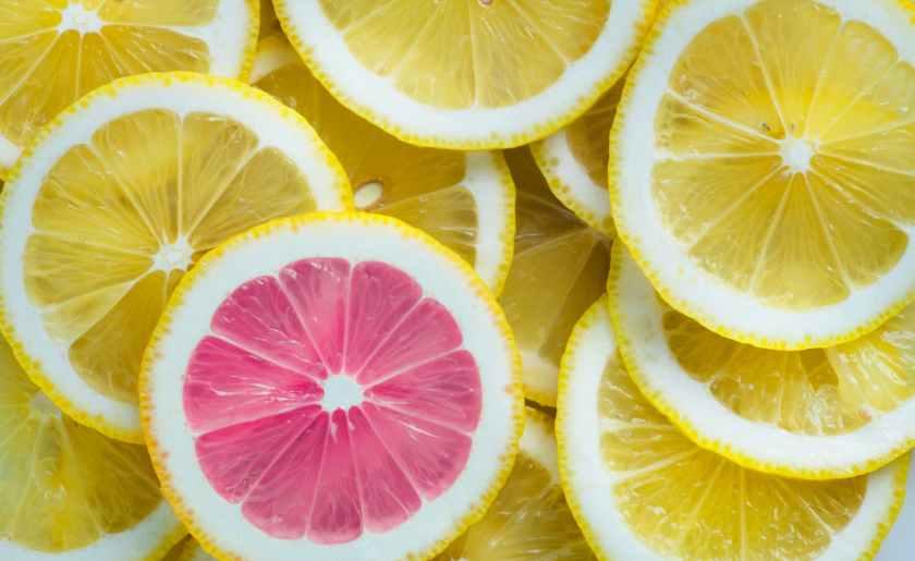 One pink lemon on top of a pile of yellow Lemons